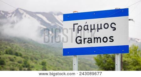 Pindus, Gramos the snowy mountain in west Greece. Destination for mountaineering. Blurred mountain and nature background. Close up view of sign with the mountain's name, panoramic.