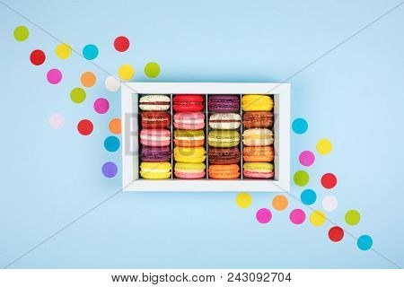 Box Of Colorful Macarons On Blue Background With Confetti. Flat Lay Style.