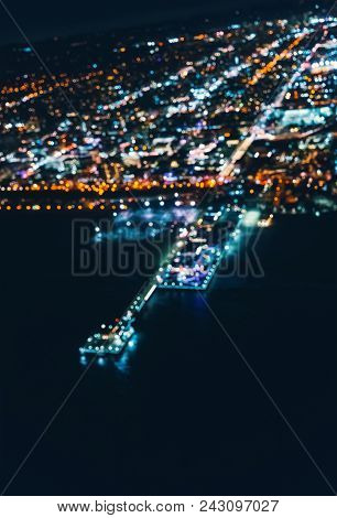 Aerial Defocused View Of The Santa Monica Shoreline, Amusment Park And Pier At Night