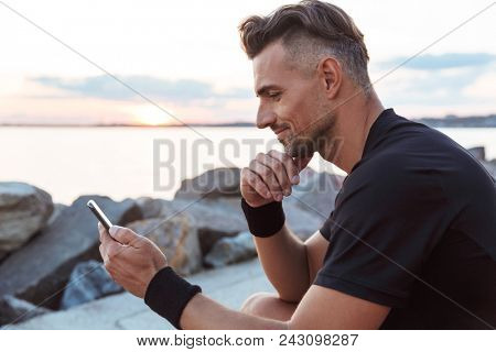 Portrait of a smiling sportsman using mobile phone while sitting at the beach