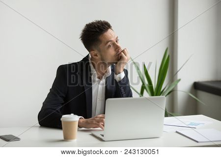 Bored Tired Millennial Businessman In Suit Feeling Dull Working On Laptop At Workplace, Absent-minde