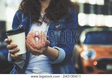 Hands Holding A White Cup With Dreank And Pink Sweet Donut In City