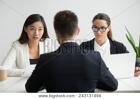 Serious Unconvinced Diverse Hr Managers Interviewing Male Job Applicant, Doubtful Strict Female Recr
