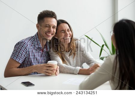 Happy couple clients laughing at funny joke meeting realtor, mortgage insurance broker or consultant, cheerful happy family customers having fun planning to sign contract buying services, taking loan poster