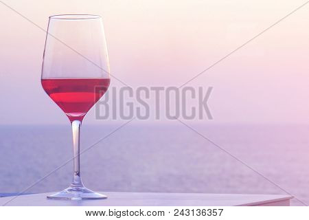 A Glass Of Red Wine Standing On A Table Near A Summer Chair Against A Background Of A Sea Horizon At