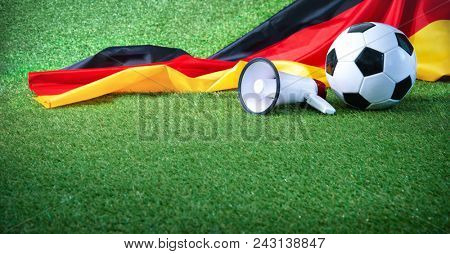 Soccer ball with german flag and megaphone on playing ground