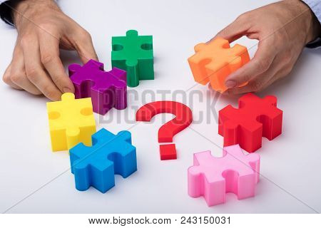 Human Hand Solving Multicolored Jigsaw Puzzle With Question Mark Sign On White Background
