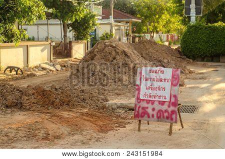 Road Sign,damaged Asphalt Road With Potholes. Bad Road. Repair,thai Language Road Sign
