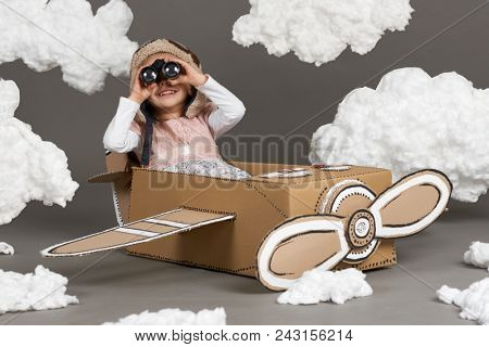 the child girl plays in an airplane made of cardboard box and dreams of becoming a pilot, clouds of cotton wool on a gray background