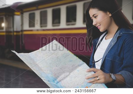 Asian Traveler Woman Looking Map At Train Station Find Destination. Happy Backpacker Girl Lost In Th