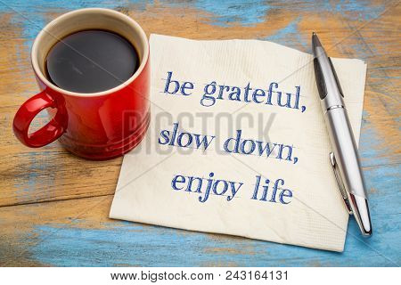 Be grateful, slow down, enjoy life - inspirational handwriting on a napkin with a cup of coffee