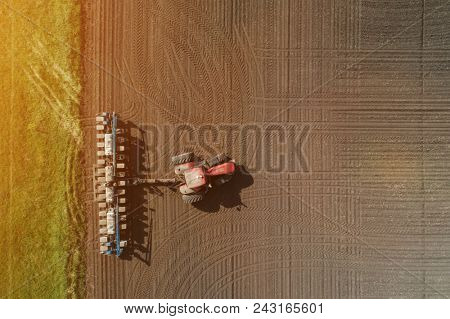 Aerial view of the tractor in the field, agricultural field work, sowing work in the field at sunset