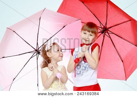 Two Charming Little Girls, Little Sister And The Eldest, Sheltered From Rain Or Sun Under Umbrellas.