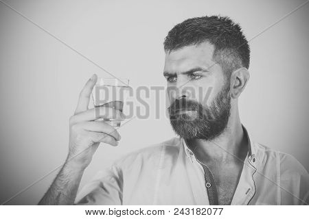 Mens heals body care. Hipster drink clean healthy water, refreshing. Hangover and thirst. Health and dieting. Life source and healthcare. Man with long beard hold water glass on yellow background. poster