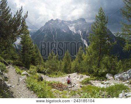 Young Woman Looking On Mountains In Front Of Her. Alps, Italy, Dolomites. Young Girl Traveler Sittin