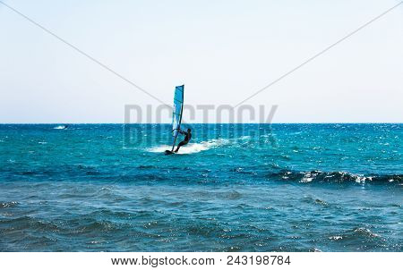Holiday Concept Image With The Blue Sea And The Blue Sky. Man On The Surfing Board Riding On The Wav
