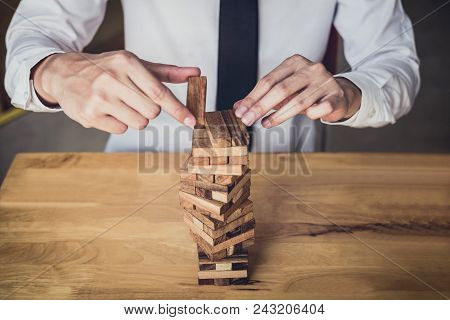 Images Of Hand Of Businesspeople Placing And Pulling Wood Block On The Tower, Alternative Risk Conce