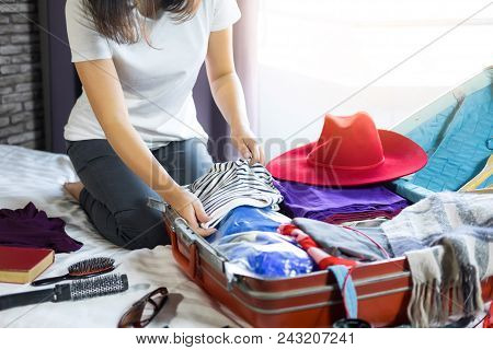 Travel And Vacation Concept, Happiness Woman Packing Stuff And A Lot Of Clothes Into Suitcase On Bed