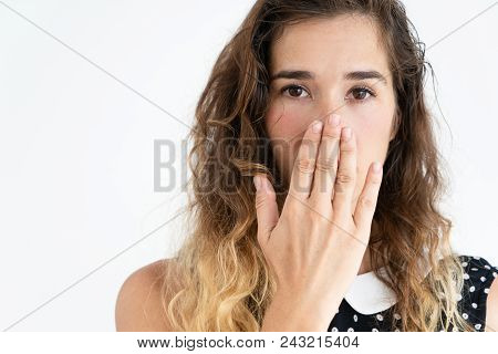 Embarrassed young pretty woman covering mouth with hand and looking at camera. Embarrassment concept. Isolated front view on white background. poster
