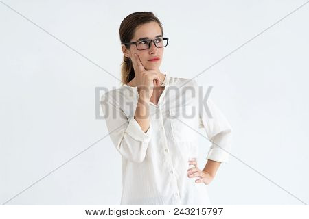 Pensive Pretty Young Woman Touching Face With Finger And Looking Away. Contemplation Concept. Isolat