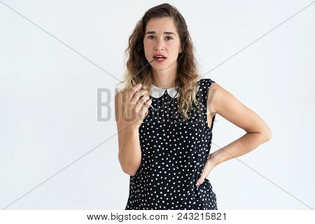Pensive Young Woman Biting Glasses Temple, Thinking And Looking At Camera. Contemplation Concept. Is