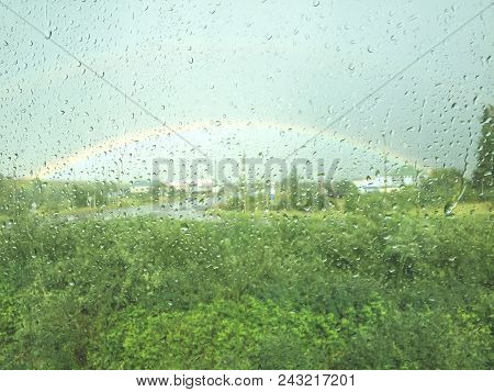 Rainbow Outside The Window. Raindrops On A Window. Rainy Days.rain-drops On A Window In Front Of A R