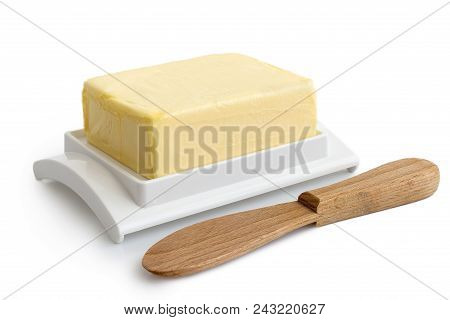 A Whole Block Of Butter On White Plastic Butter Dish Isolated On White. Wooden Butter Knife.