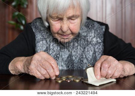 Elderly 95 Years Old Woman Sitting Miserably At The Table At Home And Counting Remaining Coins From