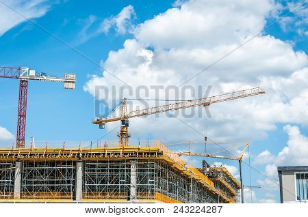 Construction Site Of New Mall Or Shopping Center In The City With Cranes Machinery, Scaffolding, Con