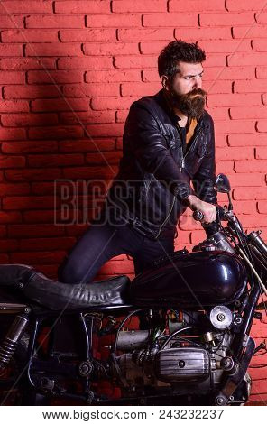 Hipster, Brutal Biker On Serious Face In Leather Jacket Gets On Motorcycle. Masculine Passion Concep