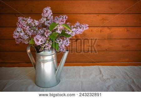 Watering Can With Branches Of Lilac Flower