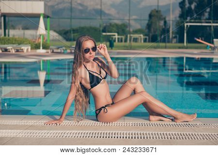 Flirty Hot Attractive Pretty Slim Fit Girl In Trendy Swim Wear And Eyewear Is Sitting In Pose Near S