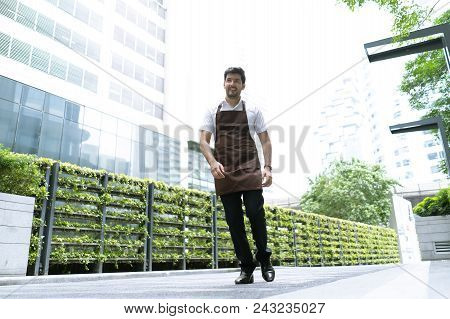 Portrait Of A Handsome And Confident Cafe Owner Standing Waitress In Brown Apron Walking In Around H