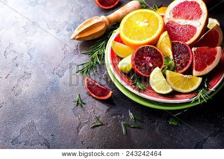 Sliced Citrus Fruit On The Plate. Citrus Salad On Stone Dark Background. Copy Space