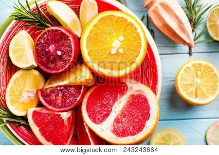Sliced Citrus Fruit On The Plate. Citrus Salad On Blue Wooden Background. Copy Space