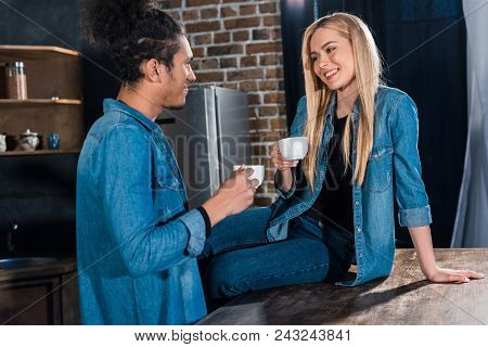 Smiling Multiracial Young Couple With Cups Of Coffee Having Conversation In Kitchen At Home