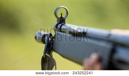 Firearm handgun in man' s hand who marks the target. Front side of weapon with close up view on blurred nature background.