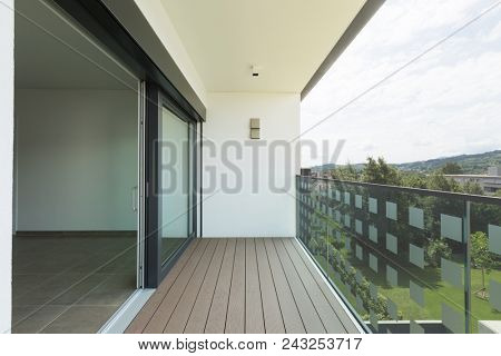 Balcony of modern apartment with white walls, nobody in the scene
