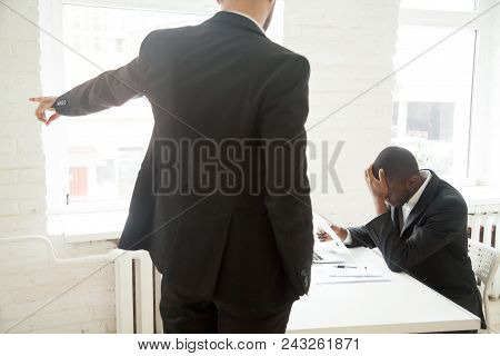 Determined Angry Employer Pointing At Door, Asking Depressed Fired African American Worker To Leave.