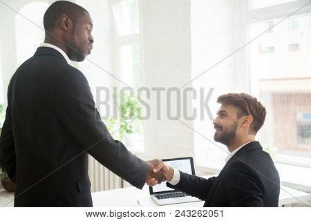 Serious African American Boss Handshaking Congratulating Proud Caucasian Subordinate With Closing Pr
