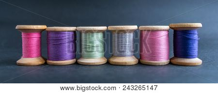 Set of pastel colors thread for sewing on a black background. Set of threads on bobbins retro style. Line coils with threads. Vintage accessories for sewing on the table. Multicolor spools of thread isolated poster