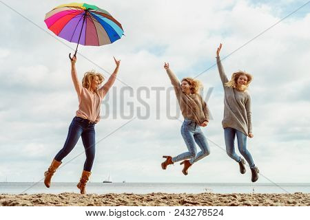 Three Women Full Of Joy Having Great Time Together. One Woman Holding Colorful Umbrella.