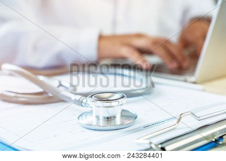 Doctor's Writing And Working On Laptop Computer, Writing Prescription Clipboard With Record Informat