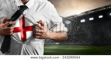 England soccer or football supporter showing flag under his business shirt on stadium.