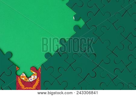Turkmenistan Flag  Is Depicted On A Completed Jigsaw Puzzle With Free Green Copy Space On The Left S