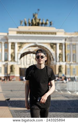 Young Stylish Man Tourist Walking Near General Staff Builsing Arch In The Palace Square In St. Peter