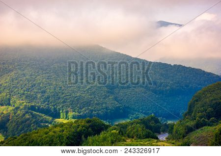 Beautiful Mountain Landscape In Low Clouds. Peak Of The Mountain In The Distance Among The Clouds. B