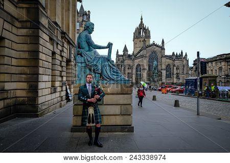 Edinburgh, Scotland - April 27, 2017: Bagpipe Player With Traditional Scottish Highlander Robes Play