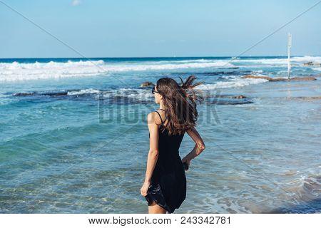 Girl Walking Along The Beach. Caucasian Woman Walks Along Beautiful Seashore