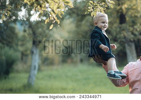 Cute Toddler Smile In Suit, Shirts, Sneakers Under Tree, Fashion. Small Boy Sit On Male Hand In Appl